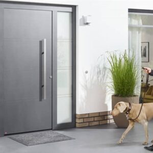 woman and dog in front of a grey front door